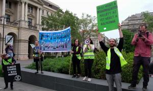 """Környezetvédelmi tüntetés a Kossuth Lajos téren. A táblán a felirat: """"Vess véget a kapitalizmusnak mielőtt az véget vet a bolygónak"""""""